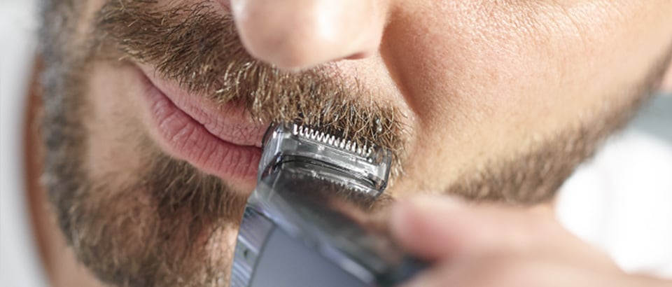 Man trimming moustache with Philips beard trimmer