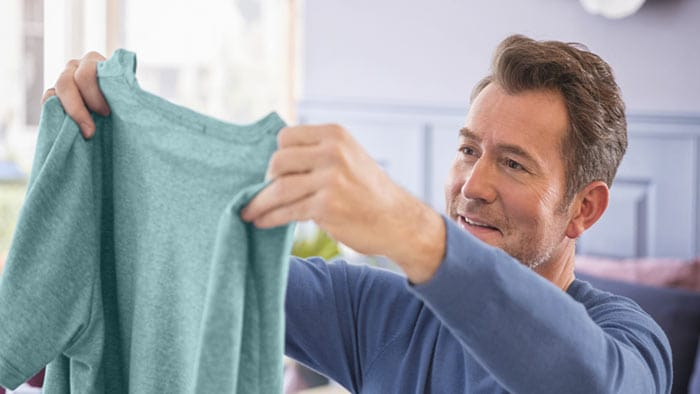 man holding up freshly washed clothes